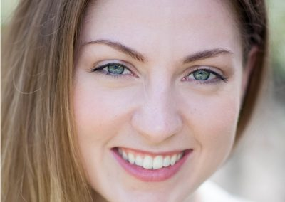 A smiling young woman with green eyes and light brown hair.